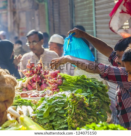 DELHI, INDIA - OCT 16: man waters his food at Chawri Bazar  on Oct 16, 2012 in Delhi, India. Established in 1840 it was the first wholesale market of Old Delhi. - stock photo