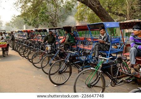 Delhi, India - October 10, 2012: Rikshaw drivers waiting for passengers at the outskirts of Old Delhi. - stock photo