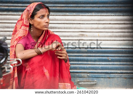 DELHI, INDIA - SEPTEMBER 14: A woman sits on the side of the road, in Delhi, India on September 14, 2010 - stock photo