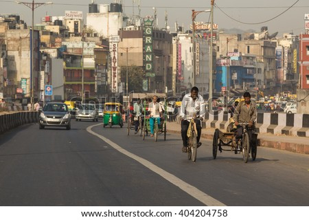 DELHI, INDIA - 19TH MARCH 2016: A view along roads in Delhi during the day showing buildings, Tuk Tuks, rickshaws, cars and people. - stock photo