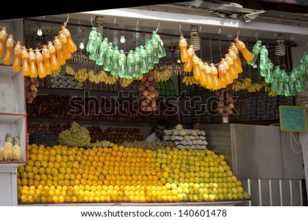 DELHI -  JANUARY 16: Juice stall owner preparing fresh fruit juices on January 16, 2013 in Coimbatore, Tamil Nadu, India. Fresh juices are great alternatives to polluted drinking water in India. - stock photo