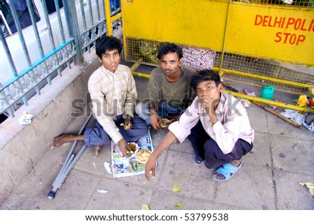 DELHI - SEP 22: Three young street kids eating on ground on September 22, 2007 in Delhi, India. UNHCHR has estimated that India has the largest population of street children in the world. - stock photo