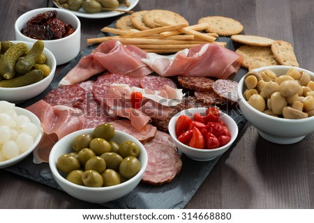 deli meat snacks, sausages and pickles on a blackboard, horizontal - stock photo