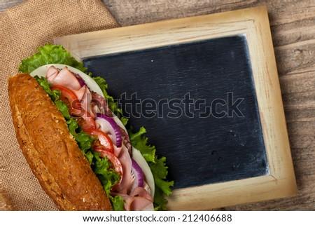 Deli sub sandwich with chalkboard. Selective focus. - stock photo
