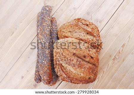 delicacy french rye breads and baguettes topped with sunflower and poppy seeds over wooden table - stock photo