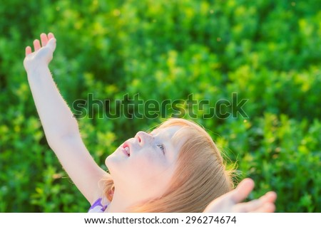 delicate and beautiful little red-haired girl holds out hands up - stock photo