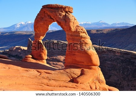 Delicate Arch  in Arches National Park near Moab, Utah. Taken at sunset in late fall, with snow on La Sal Mountains in background. - stock photo