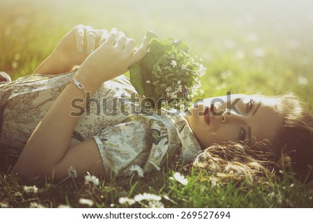 delicate beautiful young woman enjoy in sun lie in grass hold bouquet of wild flowers retro look and colors - stock photo