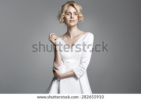 Delicate blond lady isolated from the grey background - stock photo