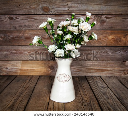 delicate bouquet of carnations in a vase on a vintage wooden background - stock photo