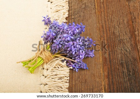 Delicate bouquet of hyacinths on the table and a piece of white paper - stock photo