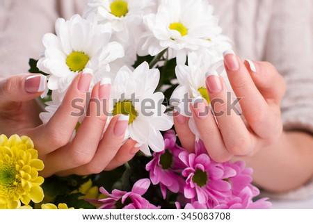 Delicate bouquet of white daisies in female hands. Classic french manicure. - stock photo