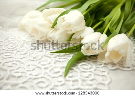 delicate bouquet of white tulips lay on a white lace