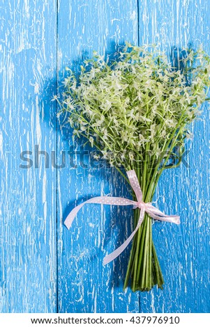Delicate bouquet of wild orchids, also known as Lesser Butterfly Orchid (Platanthera bifolia) on a blue wooden table. Vertical - stock photo