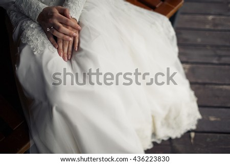 Delicate bride's hands lie on the skirt of her dress while she sits on the bench - stock photo