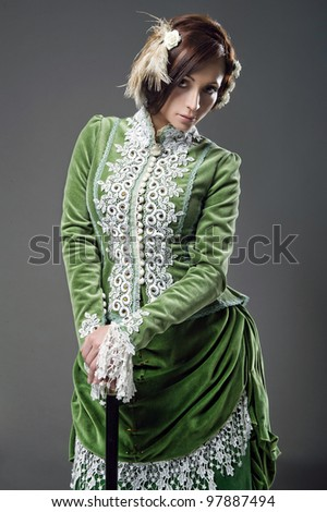 Delicate brunette with walking stick  posing in a vintage dress