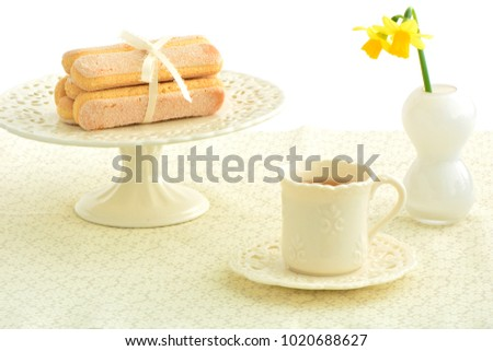 Delicate ladyfinger cookies and tea on pretty dishes in horizontal format