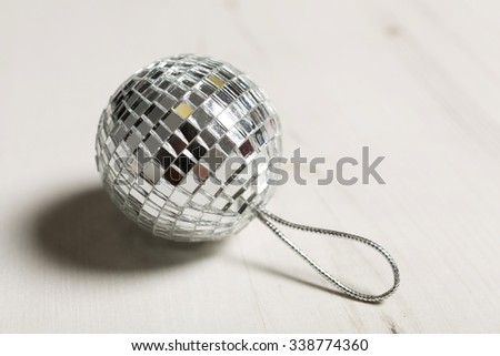 Delicate mirrored silver Christmas bauble on a light wooden surface - stock photo