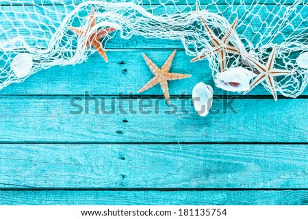 Delicate nautical border with fishing net, sea shells and starfish on a background of colourful turquoise blue painted wooden boards with copyspace for your text - stock photo