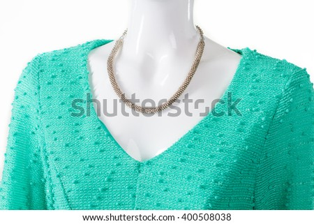 Delicate necklace with turquoise dress. Female mannequin wearing elegant jewelry. Colorful v-neck top and necklace. Expensive new merchandise. - stock photo