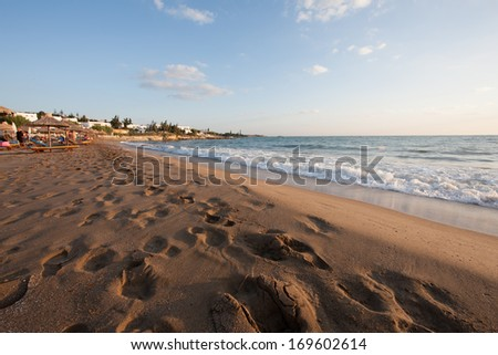 Delicate pastel sunrise over a deserted sandy beach looking across the wet sand pitted with footprints to a distant cluster of houses on the coast with gentle waves lapping the seashore - stock photo