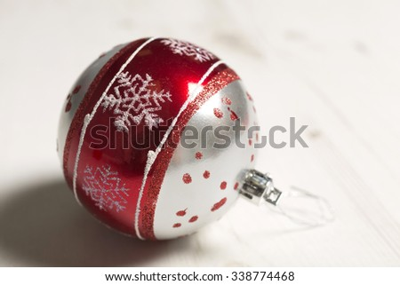 Delicate red and silver Christmas bauble with snow flakes resting light wooden surface - stock photo