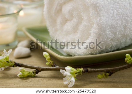 Delicate spring cherry blossoms, towel and candle  in a zen spa atmosphere - stock photo