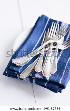 Delicate vintage silverware on blue linen napkin in a plate, antique cutlery om white wooden board background