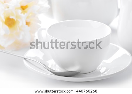 delicate white tea cup and saucer close-up with decorated background  - stock photo