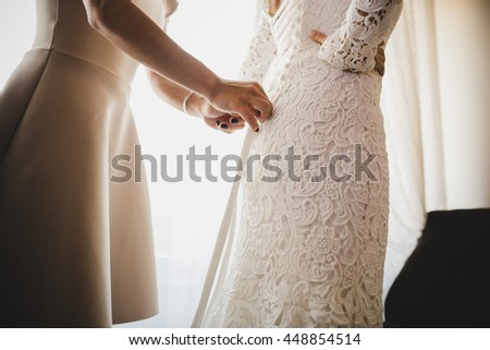 Delicate woman's hands laces a corset on the beautiful wedding dress