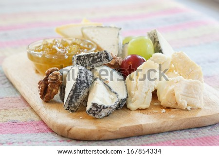 delicatessen cheeses on a wooden platter - stock photo