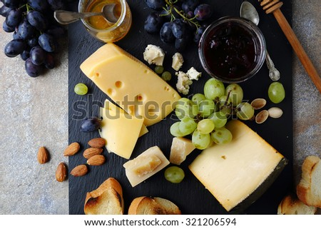 delicatessen cheeses with grapes, food top view - stock photo