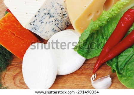 delicatessen french cheese on wooden board with hot peppers and dill isolated on white background - stock photo