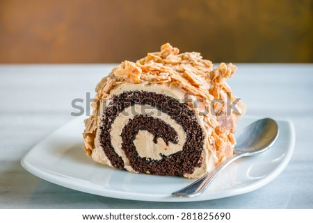 Delicious almonds roll chocolate cake on white table, on brown background - stock photo