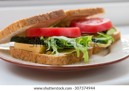Delicious and fresh vegetarian sandwich with tomatoes, cucumber, cheese and rocket salad on a wholegrain bread - stock photo