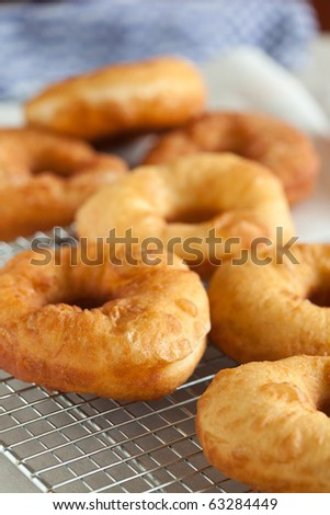 Delicious and freshly baked doughnuts cooling on a cooling rack - stock photo