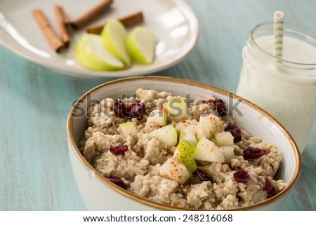 Delicious and healthy breakfast oatmeal cereal with apples and cranberries and glass of milk - stock photo