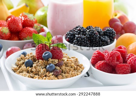 Delicious and healthy breakfast with fruits, berries and cereal on white wooden tray, close-up, horizontal - stock photo