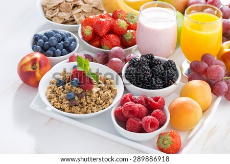 Delicious and healthy breakfast with fruits, berries and cereal on wooden table, top view - stock photo