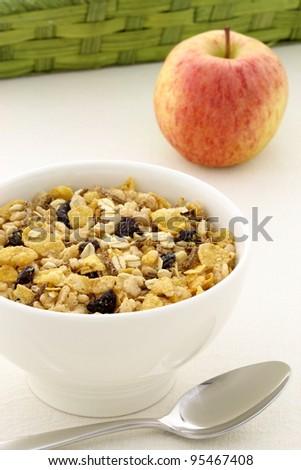 delicious and healthy granola or muesli with a fresh organic apple and lots of dry fruits, nuts and grains. - stock photo