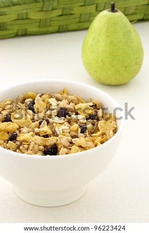 delicious and healthy granola or muesli with a fresh organic pear and lots of dry fruits, nuts and grains. - stock photo