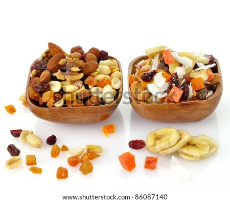 Delicious and healthy mixed dried fruit, nuts and seeds in the wooden bowls - stock photo