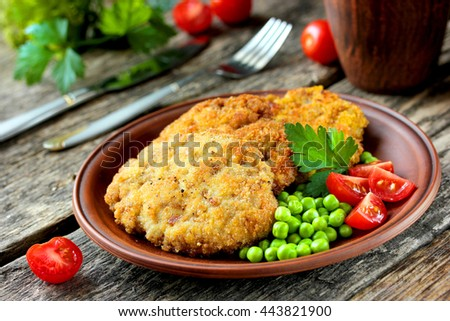 Delicious and hearty meal - fried steak in bread crumbs with tomatoes and green peas on a wooden table selective focus - stock photo