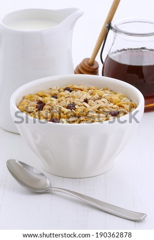 Delicious and nutritious breakfast muesli or granola cereal with milk on vintage styling. - stock photo
