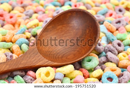 Delicious and nutritious fruit cereal loops flavorful and wooden spoon on bamboo mat, healthy and funny addition to kids breakfast  - stock photo