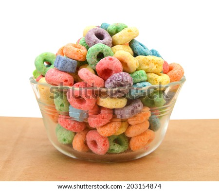 Delicious and nutritious fruit cereal loops flavorful in glass bowl on brown paper, healthy and funny addition to kids breakfast  - stock photo