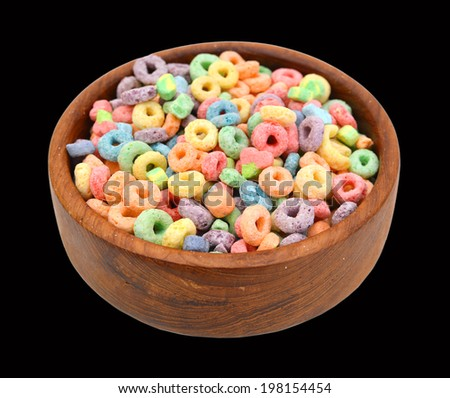 Delicious and nutritious fruit cereal loops flavorful in wooden bowl on black background, healthy and funny addition to kids breakfast  - stock photo