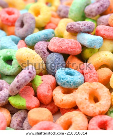 Delicious and nutritious fruit cereal loops flavorful on background, healthy and funny addition to kids breakfast  - stock photo