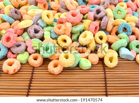 Delicious and nutritious fruit cereal loops flavorful on white background, healthy and funny addition to kids breakfast on bamboo mat  - stock photo