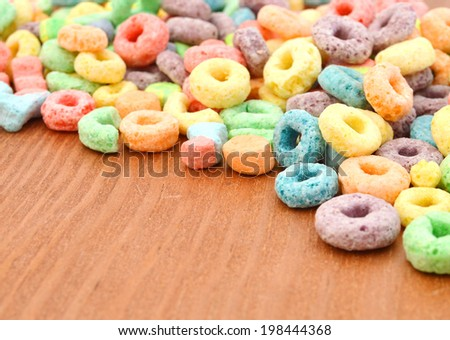 Delicious and nutritious fruit cereal loops flavorful on wooden board, healthy and funny addition to kids breakfast  - stock photo